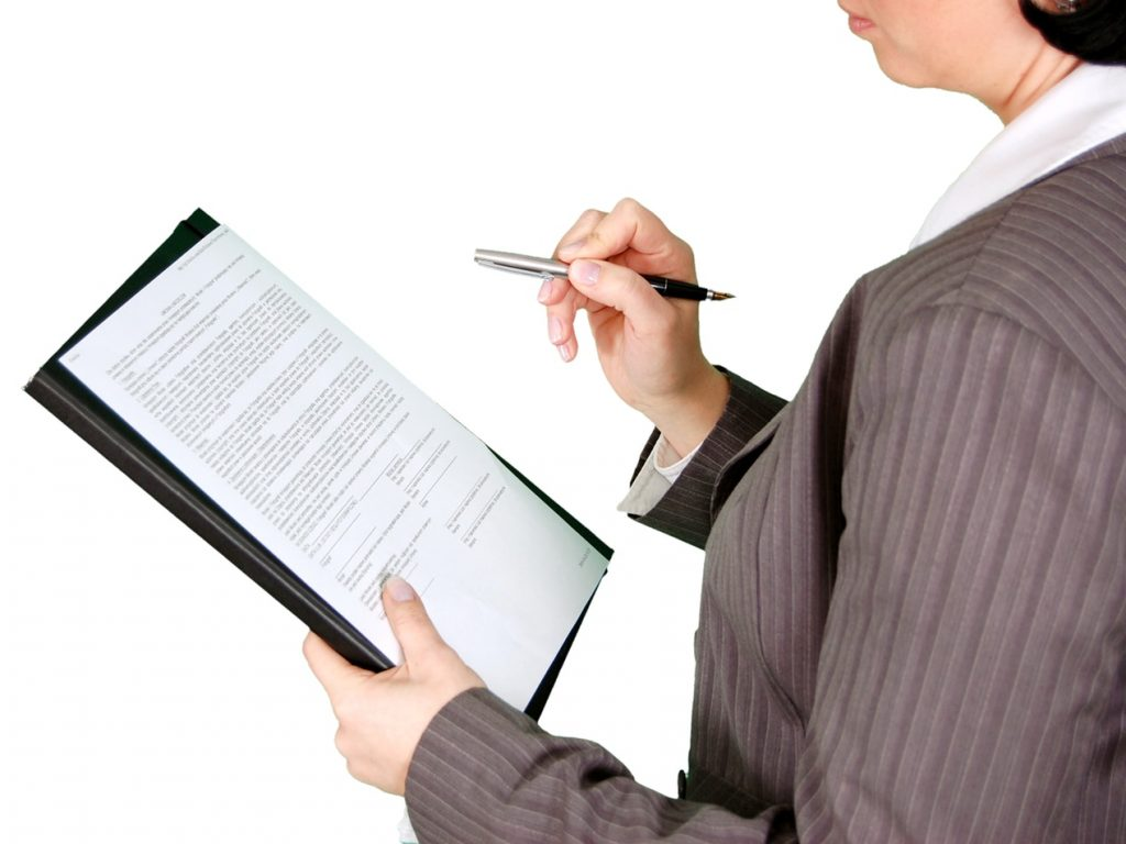Woman holding a pen to sign a legal document