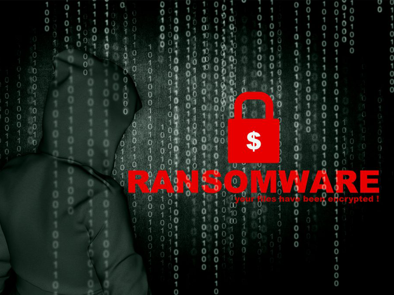 Black background with man in hoodie and numbers running vertical, and red RANSOMWARE with lock in front.