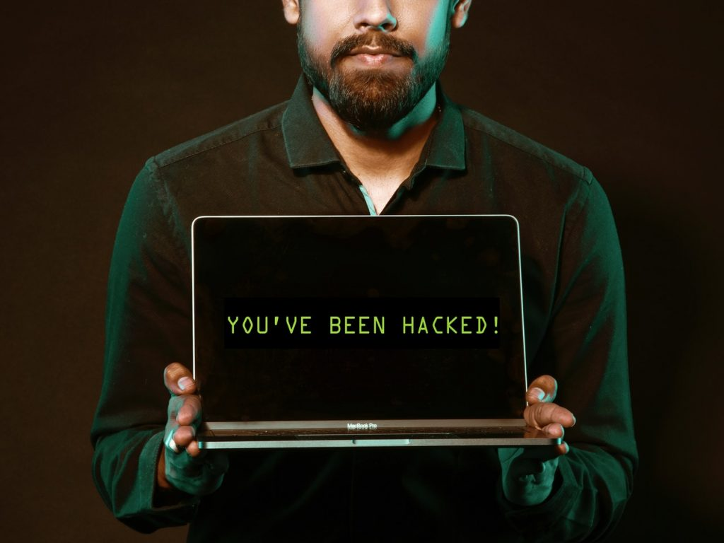 """Hacker with laptop computer displaying """"you've been hacked"""" on the screen"""