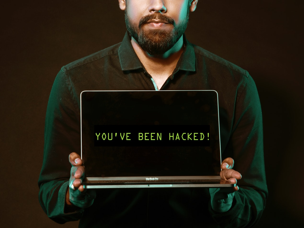 "Hacker with laptop computer displaying ""you've been hacked"" on the screen"