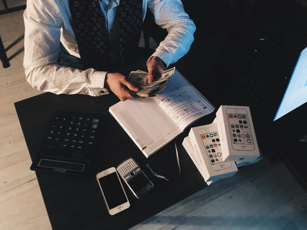 Businessperson counting money at a desk in front of smartphones and computer