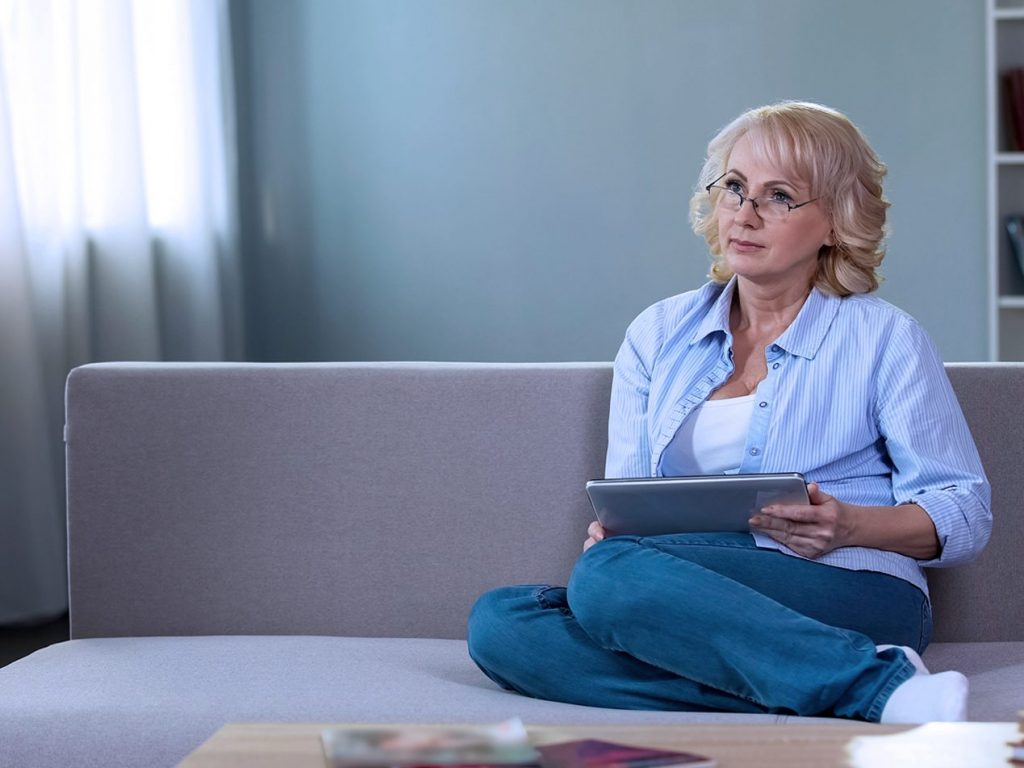 woman sitting on couch with tablet