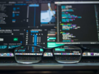 Spectacles in front of laptop with design code on the screen