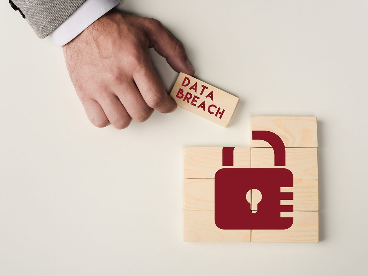 Hand putting together 8 beige rectangular blocks with the image of a red lock and 'DATA BREACH' on top.