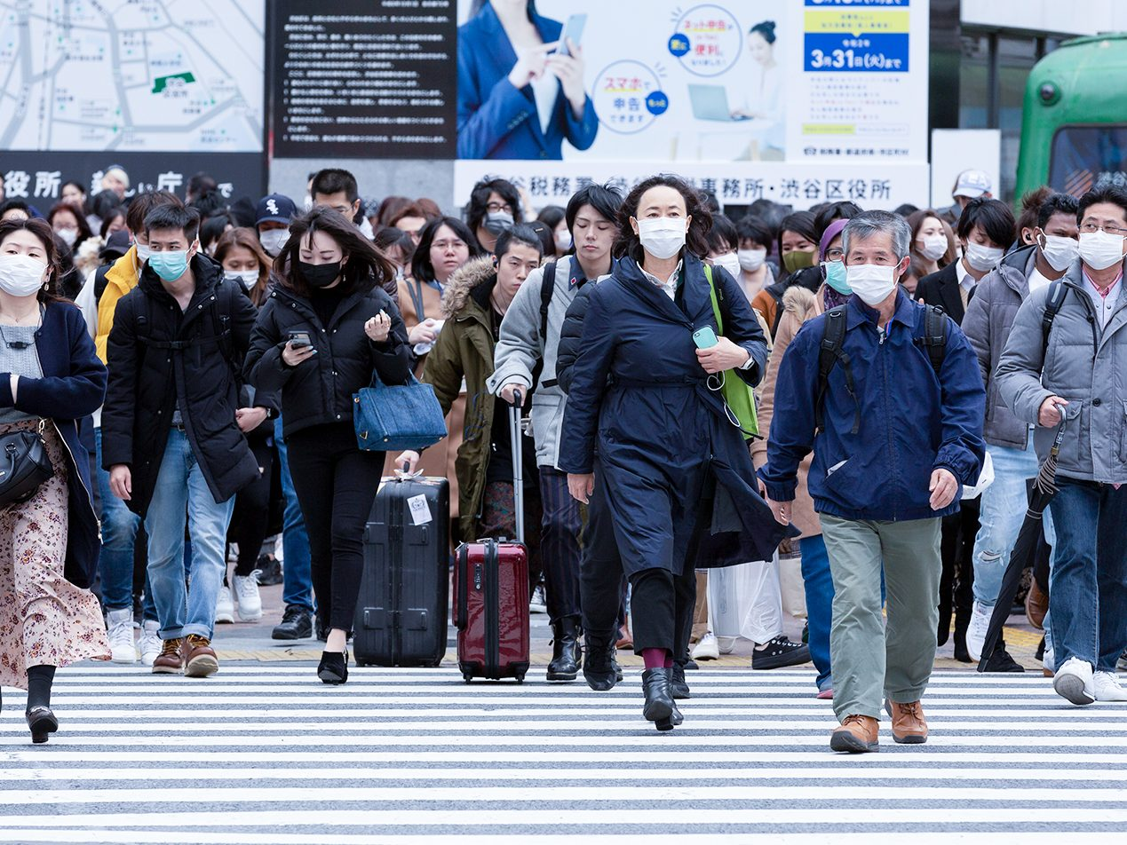 Crowded Japanese intersection with several people wearing face masks for protection