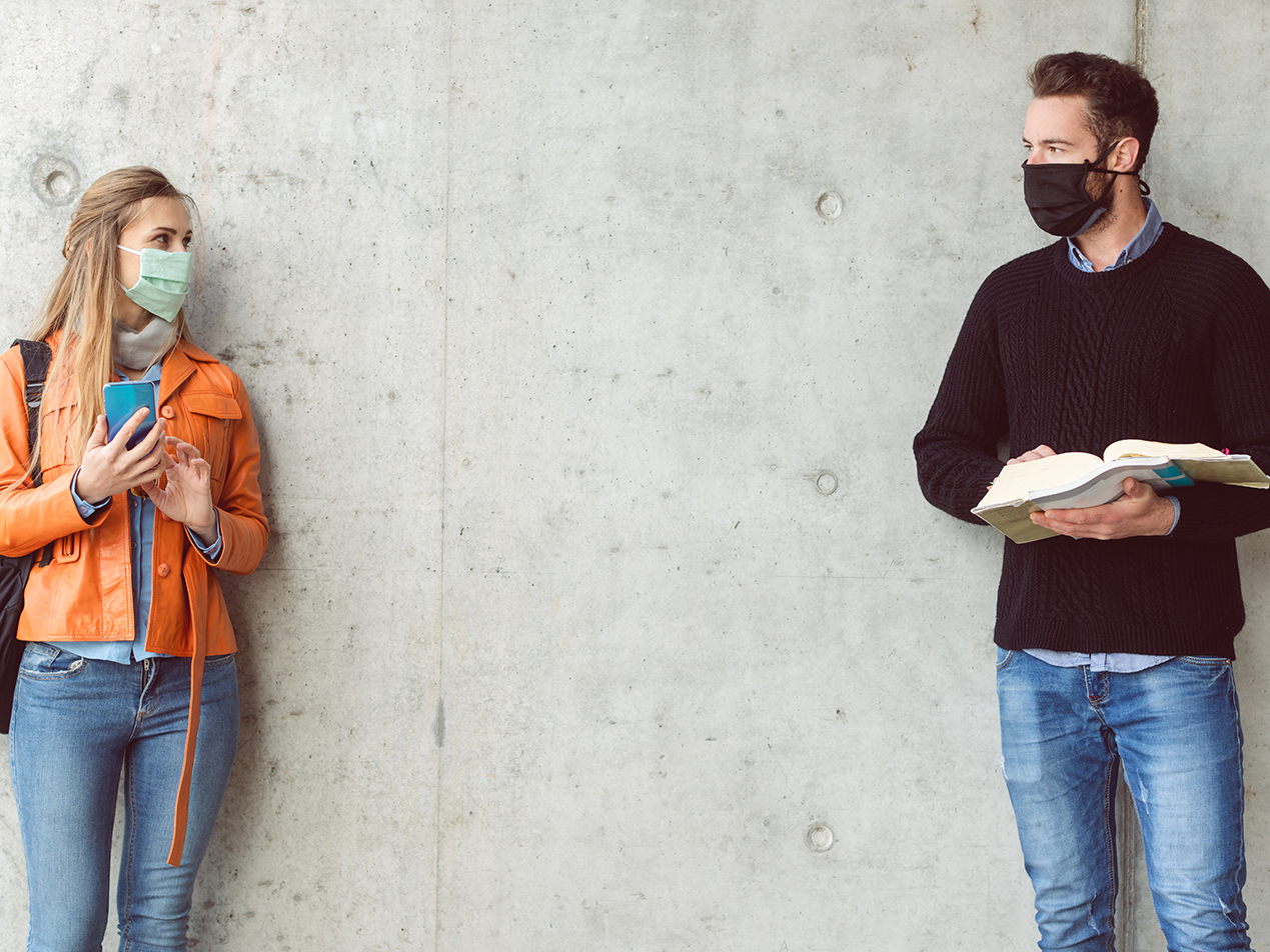 A woman and man looking at each other while social distancing and wearing face masks.